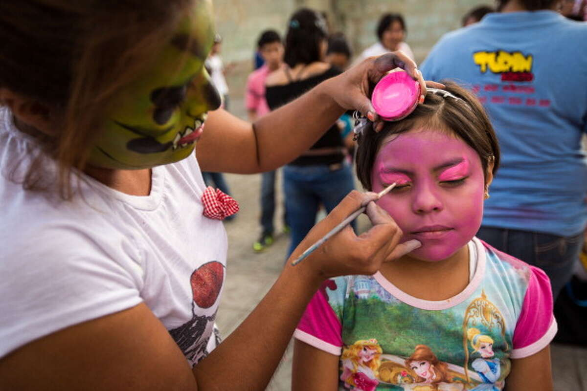 OAXACA, MEXICO - NOVEMBER 01: A young Mexican girl has her face painted to celebrate the Day of the Dead Festival on November 1, 2013 in Oaxaca, Mexico. The religious holiday, known in Spanish as Dia de los Muertos, focuses on remembering and honoring those who have died by observing traditions such as building private altars for the departed and visiting graves with gifts. (Photo by Richard Ellis/Getty Images)