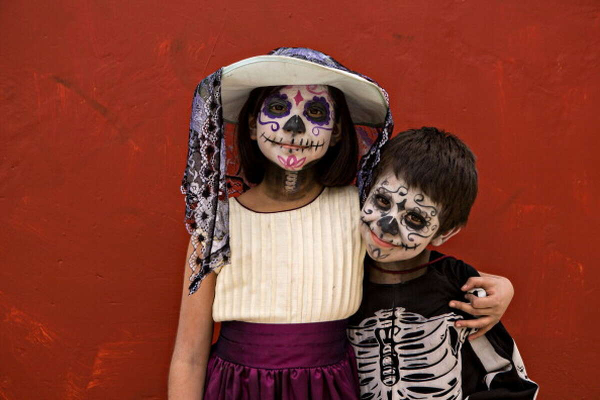 OAXACA, MEXICO - NOVEMBER 01: Young Mexican children dressed in costumes smile during the Day of the Dead Festival on November 1, 2013 in Oaxaca, Mexico. The religious holiday, known in Spanish as Dia de los Muertos, focuses on remembering and honoring those who have died by observing traditions such as building private altars for the departed and visiting graves with gifts. (Photo by Richard Ellis/Getty Images)