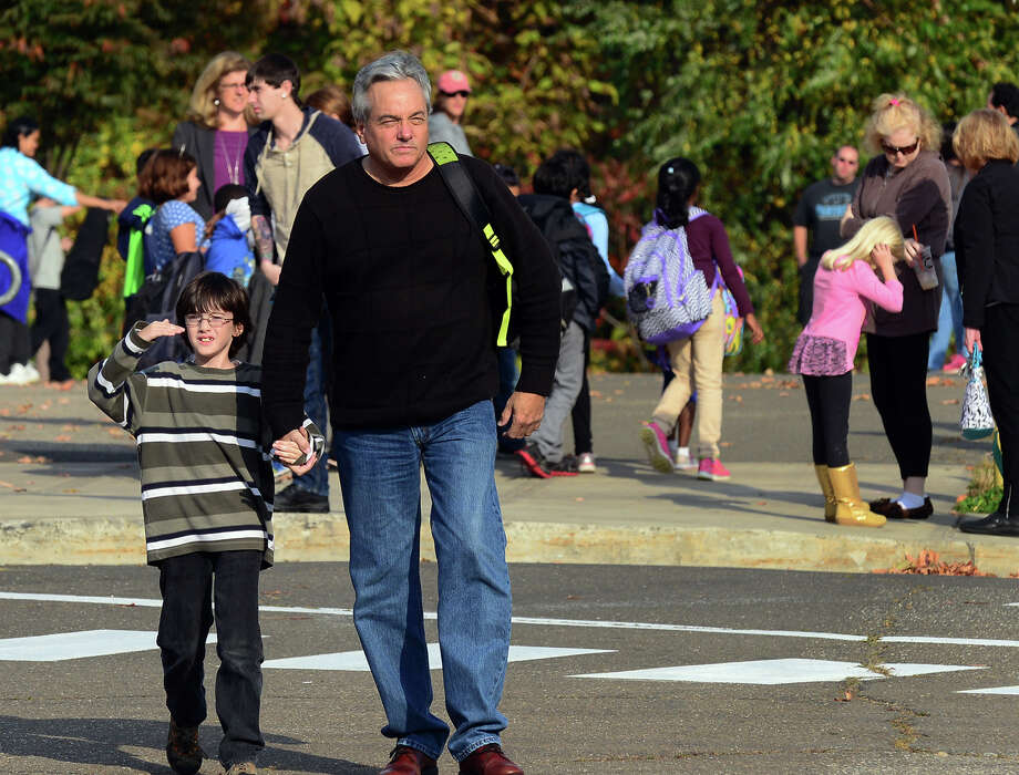 Stephen Spector pick up his son Matthew, 8, a student at Meadowside Elementary School in Milford, Conn. on Wednesday October 29, 2014. A 7-year-old girl who visited Nigeria, which is not one of the three Ebola stricken nations, has been temporarily banned from returning to Meadowside. A lawsuit is asking for $250,000 in damages and that the child be allowed to return to class at the school. Photo: Christian Abraham / Connecticut Post