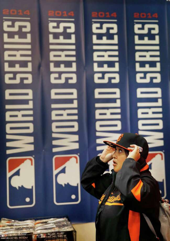 Bernadette Rosquites of San Mateo tries on a Giants cap while shopping at the Giants Dugout store at AT&T Park on Wednesday, October 29, 2014 in San Francisco, Calif.  The San Francisco Giants will play the Kansas City Royals during Game 7 of the World Series on Wednesday, October 29, 2014. Photo: Lea Suzuki / The Chronicle / ONLINE_YES
