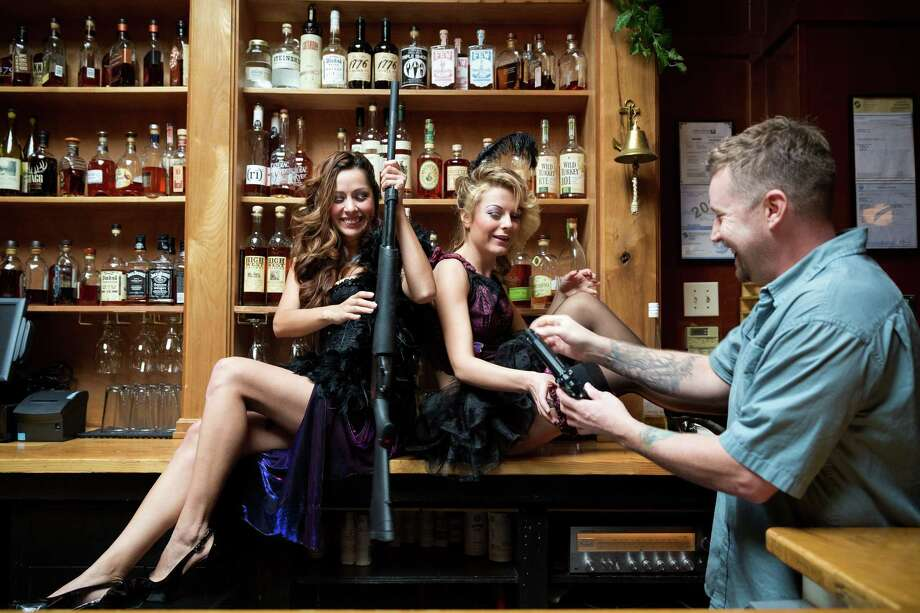 "Seattle artist Ethan Harrington, 42, right, distributes prop guns to models Kailey Anne Sommerdorf, 20, right, and Marlene Rodriguez, 27, left, before working on a piece in his 10-years-and-counting project, ""Whiskey Women,"" as photographed Thursday, Oct. 23, 2014, at The Whiskey Bar in Seattle's Belltown neighborhood. Since 2004, Harrington has painted over 60 different women within The Whiskey Bar, which will host a showing his pieces on Nov. 5, 2014. The show is open to the public. Photo: JORDAN STEAD, SEATTLEPI.COM / SEATTLEPI.COM"