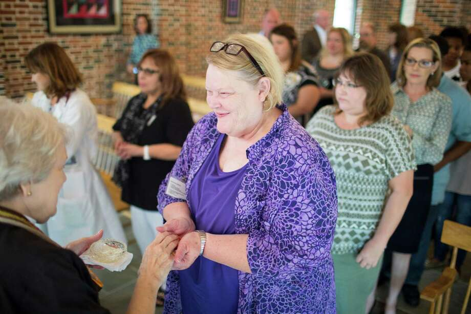 The Rev. Portia Sweet, left, leads a service at the Cockrell chapel of Houston Hospice where where she  blesses the hands of nurses, doctors and other hospice staff Wednesday, Oct. 29, 2014 in Houston. This is an annual event to honor those who aid the the dying. The process essentially is prayer and and rubbing lavender oil on the aforementioned hands. Photo: Eric Kayne, For The Chronicle / Eric Kayne