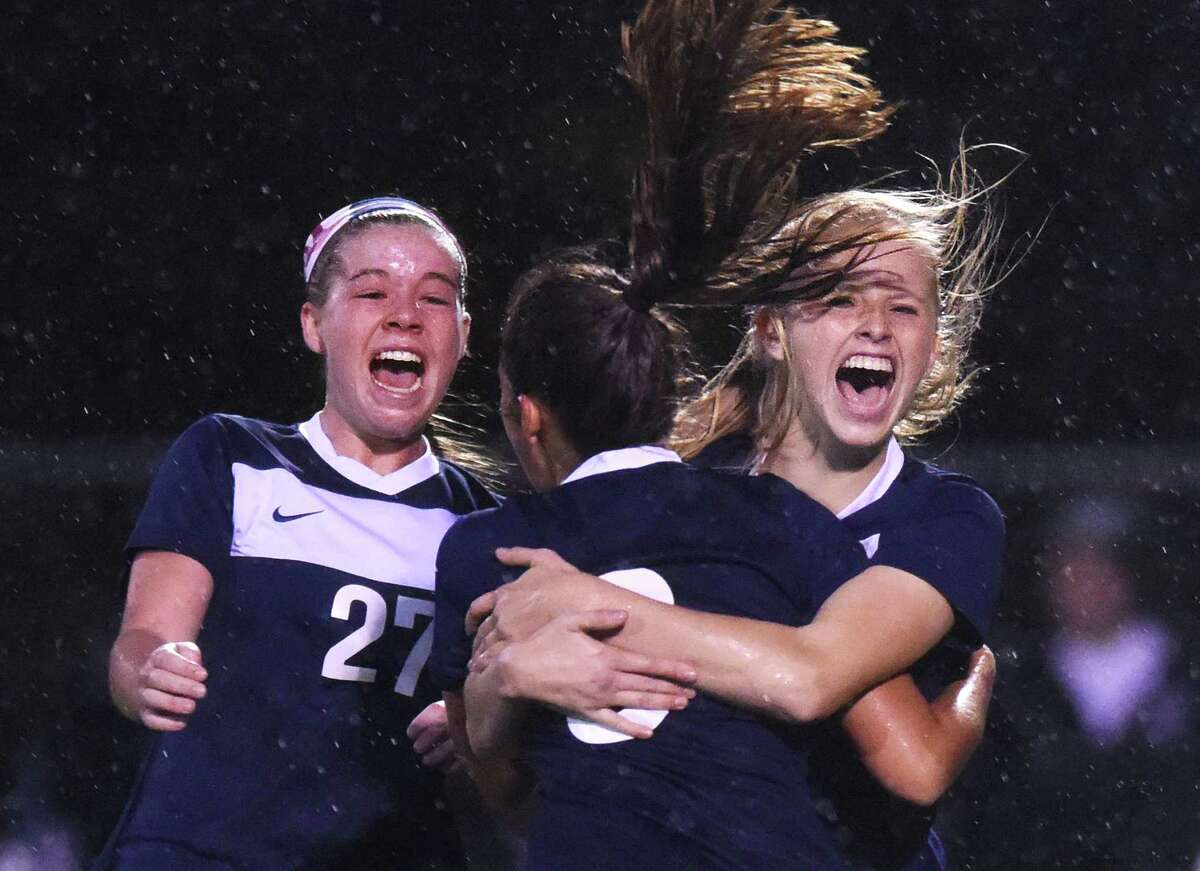 Staples' Charlotte Rossi, left, Lauren Garcia, center, and Brynly Marsh celebrate after Garcia's game-tying goal in Fairfield Warde and Staples' 1-1 double overtime tie in the FCIAC high school girls soccer championship game at Norwalk High School in Norwalk, Conn. Wednesday, Oct. 29, 2014.