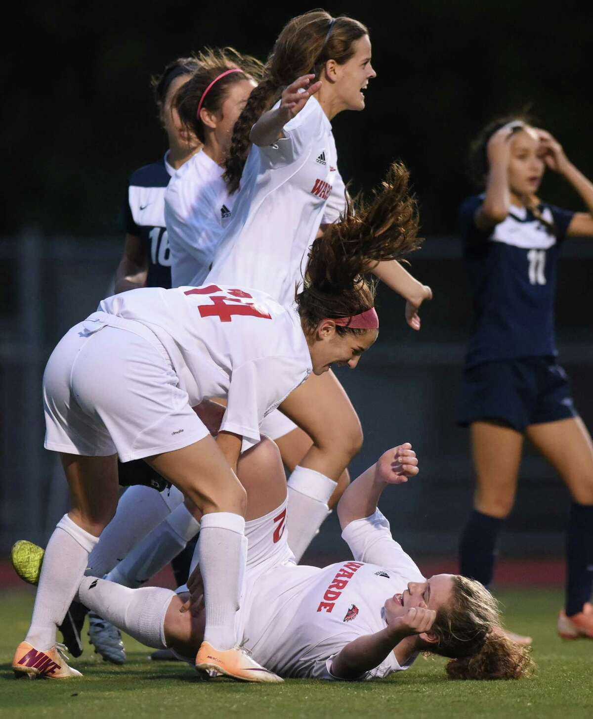 Fairfield Warde's Virginie LaRouche, top, celebrates as teammate Meredith Nerreau helps Anna Glovin off the ground after scoring a goal in Fairfield Warde and Staples' 1-1 double overtime tie in the FCIAC high school girls soccer championship game at Norwalk High School in Norwalk, Conn. Wednesday, Oct. 29, 2014.