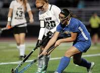 New Milford's Allison Noteware (10) and Brookfield's Jordan Deutsch (17) fight for the ball during the SWC field hockey semi finals game between New Milford and Brookfield high schools, played at Joel Barlow High School, Redding, Conn, on Wednesday, October 29, 2014.