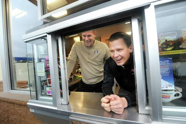 Union hockey coach Rick Bennett, left, and RPI hockey coach Seth Appert talk with a customer in the drive through on Wednesday, Oct. 29, 2014, at Dunkin' Donuts in Latham, N.Y. The coaches renew their Route 7 Rivalry as they promote their upcoming hockey games against each other. (Cindy Schultz / Times Union) Photo: Cindy Schultz / 00029238A