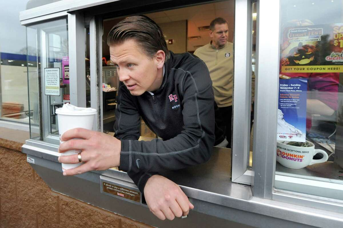 RPI hockey coach Seth Appert hands off a coffee in the drive through on Wednesday, Oct. 29, 2014, at Dunkina€™ Donuts in Latham, N.Y. Coach Appert and Union hockey coach Rick Bennett, in the background, renew their Route 7 Rivalry as they promote their upcoming hockey games against each other. (Cindy Schultz / Times Union)
