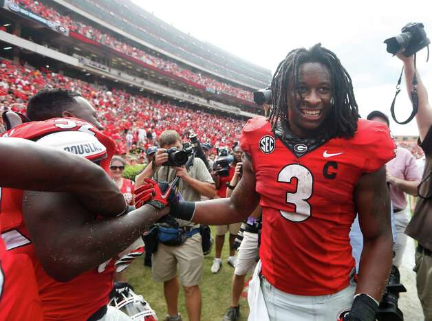 FILE - In this Sept. 27, 2014, file photo, Georgia running back Todd Gurley (3) celebrates with linebacker Amarlo Herrera (52) after an NCAA college football game against Tennessee in Athens, Ga. No. 9 Georgia continues to await word from the NCAA on the status of star tailback Todd Gurley for Saturday's game against Florida. Georgia has asked for the reinstatement of Gurley, who has acknowledged mistakes and has been suspended the last two games for an alleged violation of NCAA rules. (AP Photo/John Bazemore, File) ORG XMIT: NY162 Photo: John Bazemore / AP