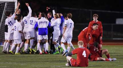Greenwich players react in disappointment as Fairfield Ludlowe celebrates its 1-0 win over Greenwich in the FCIAC high school boys soccer championship game at Norwalk High School in Norwalk, Conn. Wednesday, Oct. 29, 2014.