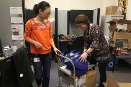 Dr. Ethel Wu (left) checks personal protective equipment from Direct Relief with research assistant Brett Lewis at UCSF  in San Francisco, Calif., on Wednesday, October 29, 2014.  Dr. Wu is leaving for Liberia tomorrow and is picking up protective equipment which will be used by the three UCSF doctors leaving to battle the Ebola epidemic.