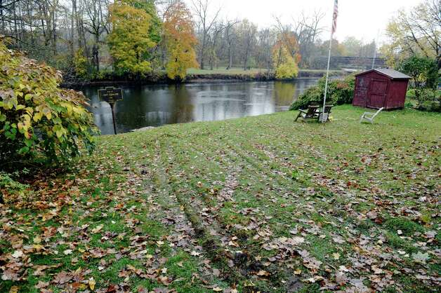 A view of the lawn at the end of Edward St. with tire tracks, seen here on Wednesday, Oct. 29, 2014, in Fort Edward, N.Y.  Alleged serial rapist, Gregory Lewis, of Southbridge, Mass., drove his vehicle down over the grass and into the Hudson River before being arrested late Tuesday night.  Lewis was wanted in eight states.  (Paul Buckowski / Times Union) Photo: Paul Buckowski / 00029257A