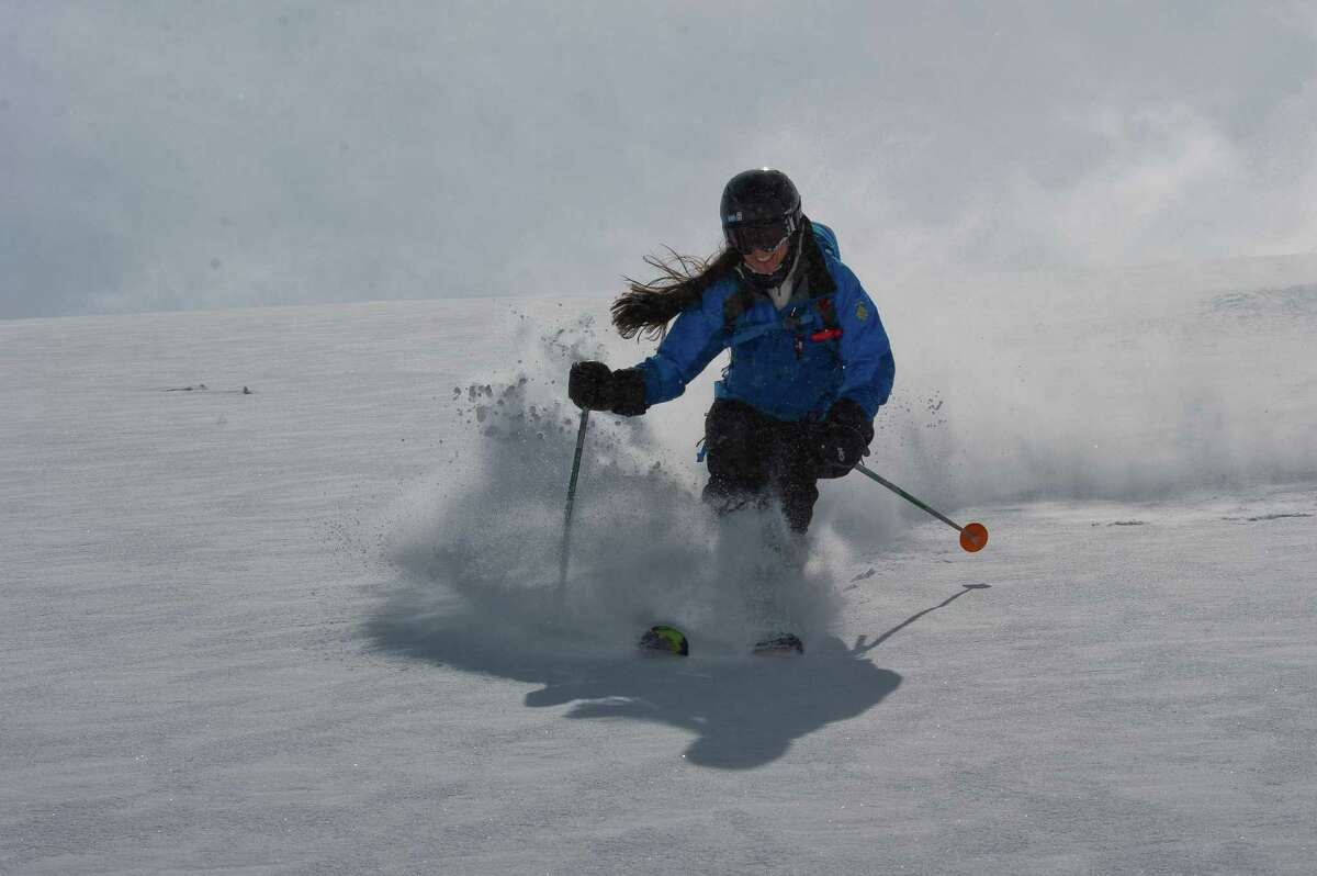 Students learn to ski powder accessed by helicopter in CMH Powder 101 camps.