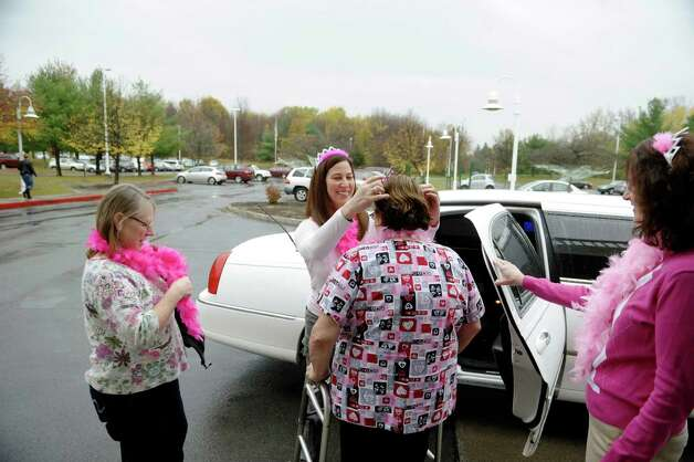 Evergreen Commons Nursing Home employees, Donna Hopkins, left, R.N. and assistant director of nursing, Kari Neubauer, second from left, director of human resources, Deb DeLuke, third from left, R.N. unit manager and Debbie Jakob, with human resources, put on crowns and pink pink feather boas before getting into a limousine on Wednesday, Oct. 29, 2014, in East Greenbush, N.Y.  On Wednesday female employees at Evergreen Commons Nursing Home were able to take time off from work to get mammography screening at a local imaging center. (Paul Buckowski / Times Union) Photo: Paul Buckowski / 00029246A