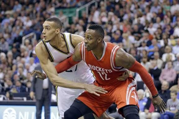 Utah Jazz's Rudy Gobert, left, guards Houston Rockets' Dwight Howard (12) in the first half during an NBA basketball game Wednesday, Oct. 29, 2014, in Salt Lake City. (AP Photo/Rick Bowmer)