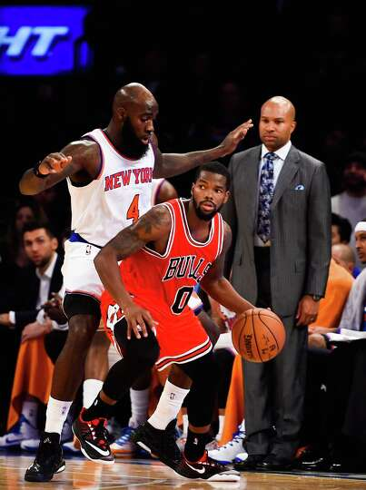 NEW YORK, NY - OCTOBER 29: Quincy Acy #4 of the New York Knicks guards Aaron Brooks #0 of the Chicag
