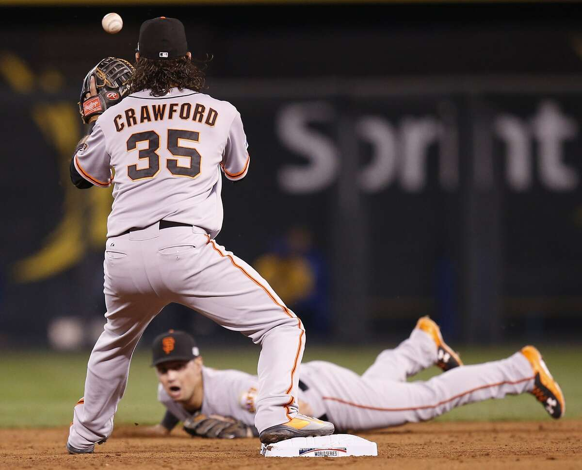Giants Joe Panik flips the ball from his glove to Brandon Crawford on a double play in the third inning during Game 7 of the World Series at Kauffman Stadium on Wednesday, Oct. 29, 2014 in Kansas City, Mo.