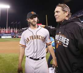 Giants pitching coach Dave Righetti puts his arm around Giants Madison Bumgarner after the Giants defeated the Royals 3 to 2 to win the World Series in Game 7 of the World Series at Kauffman Stadium on Wednesday, Oct. 29, 2014 in Kansas City, Mo.
