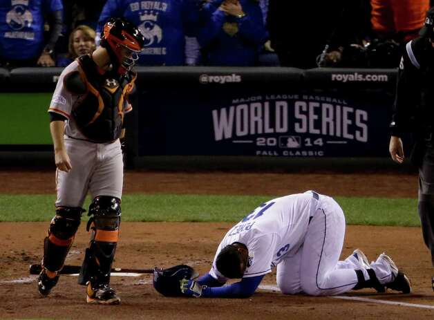 Kansas City Royals Salvador Perez, right, lies on the ground after being hit by pitch by San Francisco Giants Tim Hudson as catcher Buster Posey looks on during the second inning of Game 7 of baseball's World Series Wednesday, Oct. 29, 2014, in Kansas City, Mo. (AP Photo/Charlie Riedel)  ORG XMIT: WS531 Photo: Charlie Riedel / AP