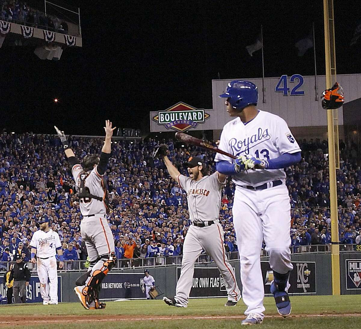 Giants Buster Posey and Madison Bumgarner celebrate the last out on a pop up by Royals Salvador Perez stranding the tying run on third base in Game 7 of the World Series at Kauffman Stadium on Wednesday, Oct. 29, 2014 in Kansas City, Mo.