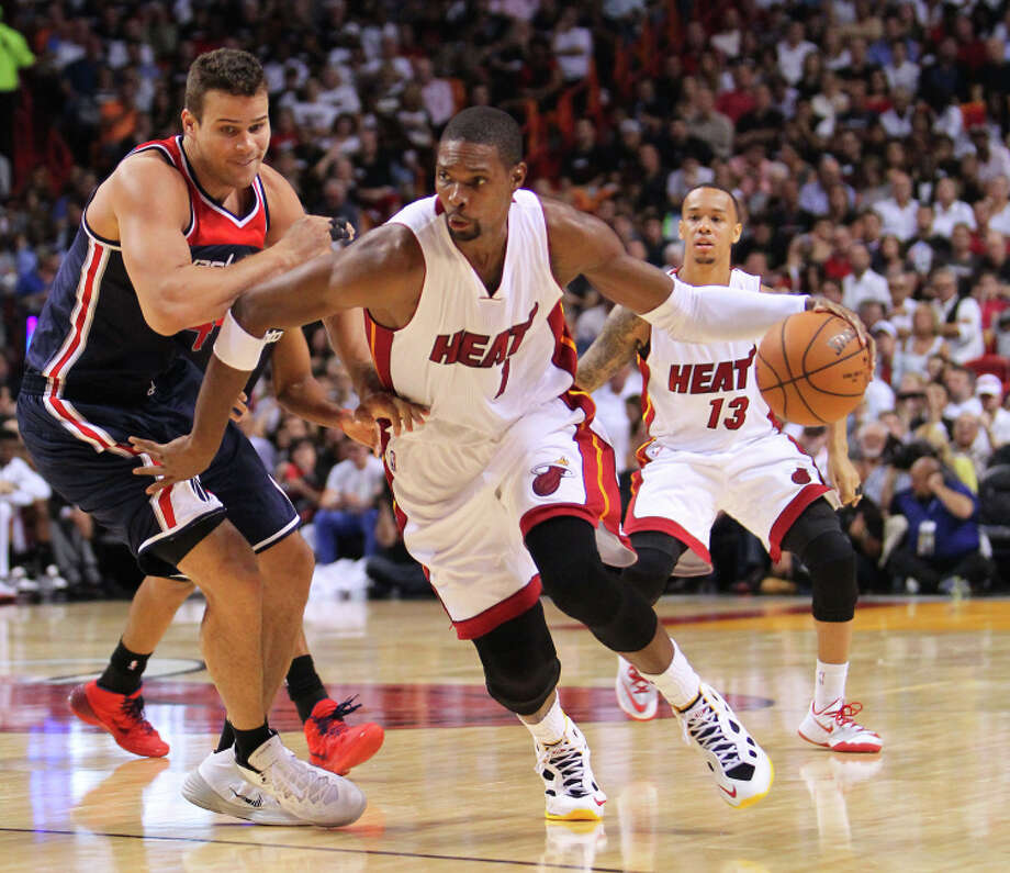 Miami's Chris Bosh drives against Washington's Kris Humphries on his way to 26 points. Photo: David Santiago / McClatchy-Tribune News Service / El Nuevo Herald