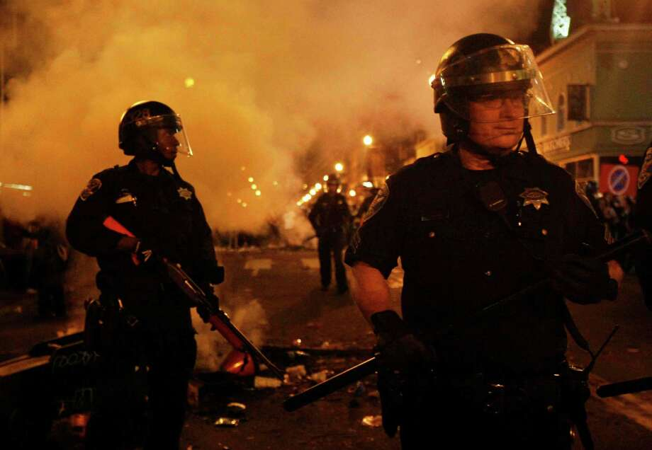 A riot police officer tries to tame the scene after Giants fans riot in the streets at 22nd and Mission after the San Francisco Giants win the World Series against the Kansas City Royals Wednesday, October 29, 2014. Photo: Jessica Christian / The Chronicle / ONLINE_YES