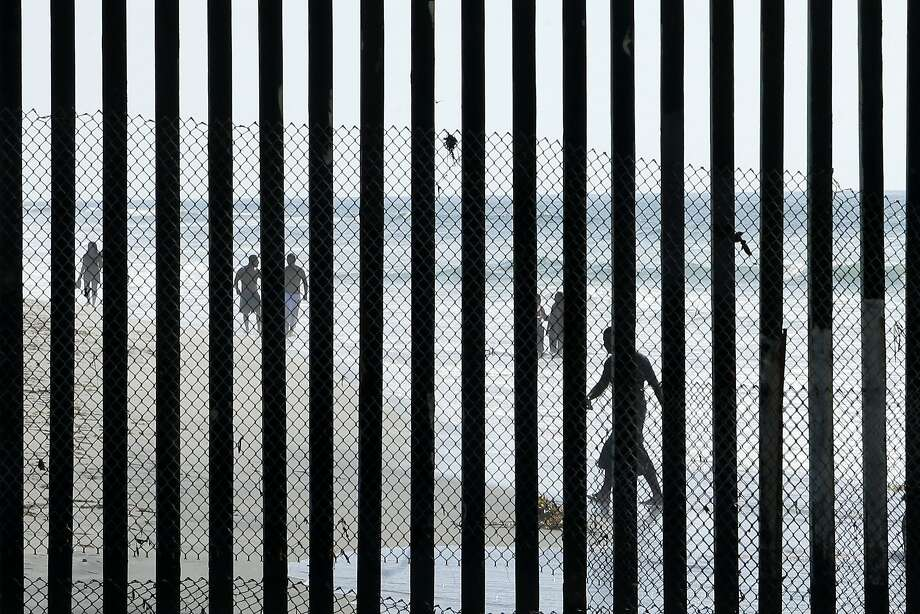 People walk along the beach in Tijuana, Mexico, where metal bars marking the border with the United States meet the sea Wednesday, Oct. 29, 2014, as seen from San Diego.  (AP Photo/Gregory Bull) Photo: Gregory Bull, Associated Press