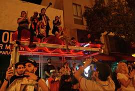 Giants fans climb a Muni bus stop near 22nd and Mission streets after the World Series victory against the Kansas City Royals on Oct. 29, 2014.