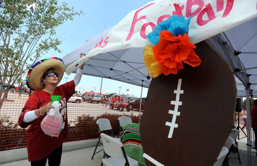 Lamar fan and alumni Catherine Klein straightens out a sign at the Merrill Lynch Cardinal Cantina Fo