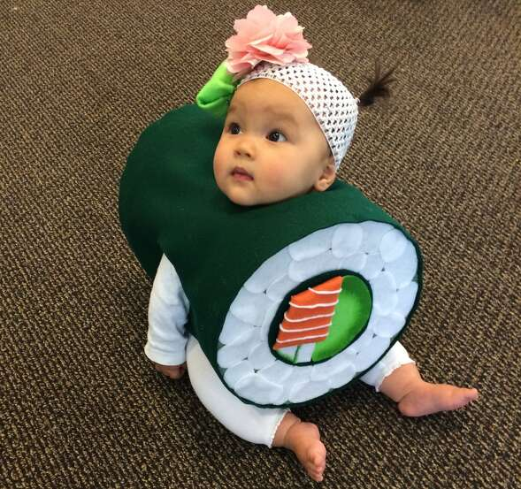"SUSHI ROLL: We've received many orders of baby sushi over the years, but this is a memorable technical costuming triumph. Amy Jeschke writes: ""Many people agree that sushi is delicious, and many people agree that babies are delicious. So what could be better than a baby in a sushi roll?! After several late nights and more than several glasses of wine, we have baby sushi (complete with wasabi and ginger headband)!"""