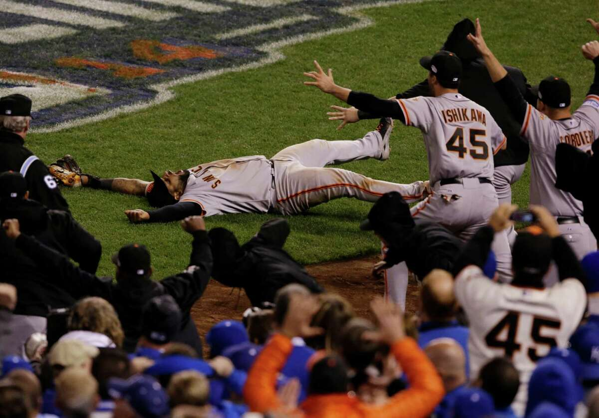 Teammates celebrate as San Francisco Giants Pablo Sandoval catches the last out a pop fly by Kansas City Royals Salvador Perez during the ninth inning of Game 7 of baseball's World Series Wednesday, Oct. 29, 2014, in Kansas City, Mo. The Giants won 3-2 to win the series. (AP Photo/Orlin Wagner)