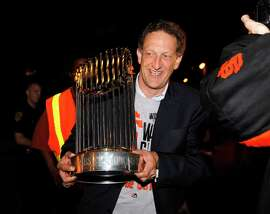 Team CEO Larry Baer carries the championship trophy to show the fans who greeted the Giants when they arrived back at AT&T Park in San Francisco on Thursday.