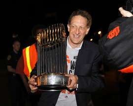 Team CEO Larry Baer carries the championship trophy to show the fans who greeted the Giants when they arrived back at AT&T Park in San Francisco, Calif. on Thursday, Oct. 30, 2014 after beating the Kansas City Royals in Game 7 of the World Series.