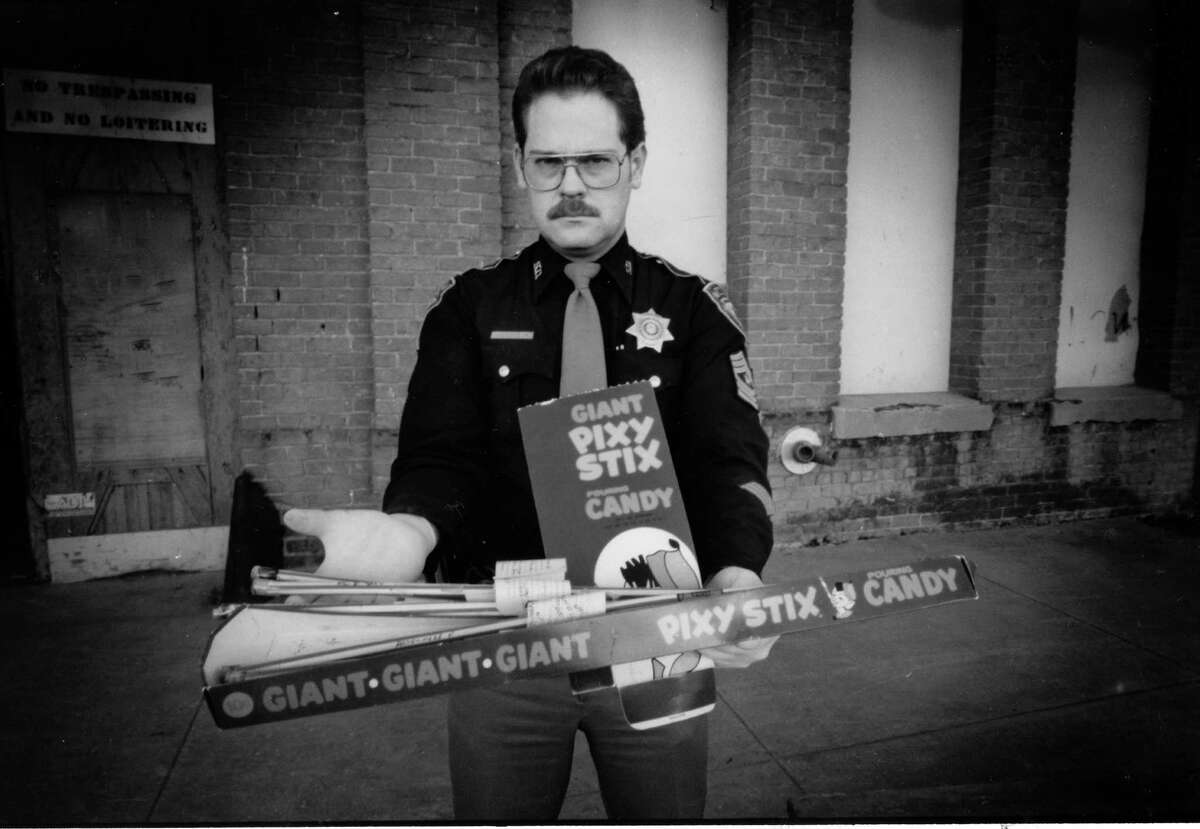 JAN 1986 - SHERIFF'S SGT. D.F. MORGAN WEARS SURGICAL GLOVES TO PROTECT HIM FROM POISON IN RONALD CLARK O'BRYAN'S DETERIOTATING PIXY STIX. HOUCHRON CAPTION (10/29/2004) SECNEWS: LETHAL: In 1986, a Harris County sheriff's deputy had to wear surgical gloves for protection from the poison in Ronald Clark O'Bryan's deteriorating Pixy Stix. (COLOR NEGATIVES ARE AVAILABLE OF THIS PHOTO)