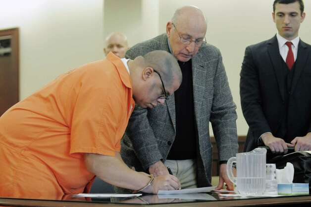 Convicted murderer, Oscar Valcarcel, left, signs a notice of appeal as his attorney Mike Feit looks on at his sentencing  on Thursday, Oct. 30, 2014, in Albany County Court in Albany, N.Y.  Last month, a jury convicted Oscar Valcarcel of first-degree murder for killing Caleb Capen, 27, during a Dec. 4 attack at Capen's 326 Western Ave., home.  (Paul Buckowski / Times Union) Photo: Paul Buckowski / 00029270A