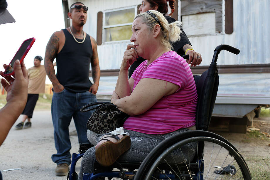 Surrounded by family and concerned members of the community trying to find ways to help her, Judy Salazar sits next to her mobile home in Mission Trails Mobile Home Park in San Antonio on Wednesday, Oct. 22, 2014. The structure of the mobile home began coming apart when it was in the moving process from Mission Trails to Lackland Village RV Park and was left in the road after repeated attempts to move it were unsuccessful. Salazar and her husband have been living in it for several days without running water or electricity. Photo: Lisa Krantz / SAN ANTONIO EXPRESS-NEWS