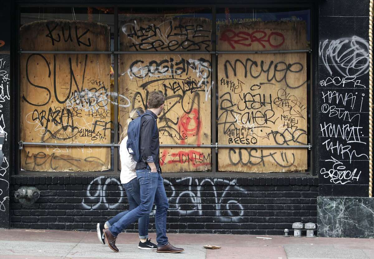 Pedestrians walk past a graffiti covered storefront on Mission Street in San Francisco, Calif. on Thursday, Oct. 30, 2014 after the Giants beat the Kansas City Royals in the World Series. The celebration turned ugly when crowds became unruly and vandalized several businesses and vehicles.