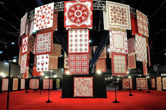 Read-and-white quilts hang from the rafters of the George R. Brown Convention Center as part of the International Quilt Festival Houston.