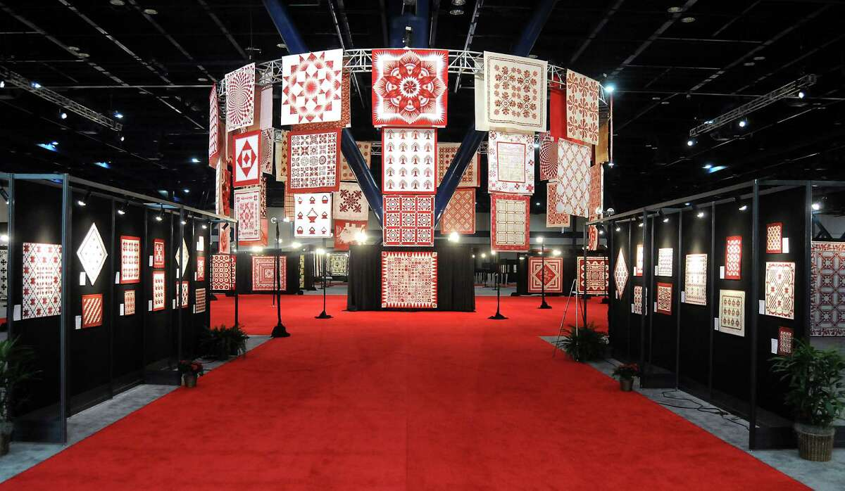 Red-and-white quilts, hanging from the rafters of the George R. Brown Convention Center, greet visitors to the International Quilt Festival Houston.