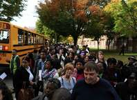 A crowd of supporters line Mitchell Drive Thursday, Oct. 30, 2014, in hopes of seeing Michelle Obama rally for the vote at Wilbur Cross High School in New Haven, Conn.