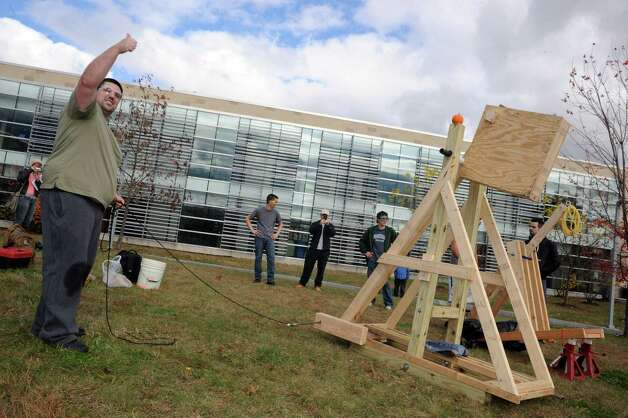 HVCC engineering student Nick Bosco, left, on team Excellence gives the thumbs up for firing of their pumpkin launcher during the Pumpkin Palooza Fall Festival for Students and Community at Hudson Valley Community College on Thursday Oct. 30, 2014 in Troy, N.Y. (Michael P. Farrell/Times Union) Photo: Michael P. Farrell / 00029264A