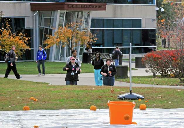Students watch as HVCC engineering student team Awesome just falls short of their target bucket during the  pumpkin launch as part of the Pumpkin Palooza Fall Festival for Students and Community at Hudson Valley Community College on Thursday Oct. 30, 2014 in Troy, N.Y. (Michael P. Farrell/Times Union) Photo: Michael P. Farrell / 00029264A