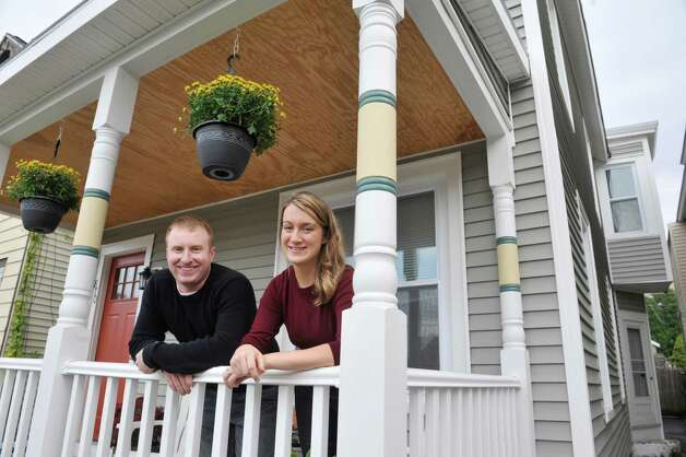 Couple, Ben and Becky Comish pose for a photograph on the porch of a home they rent out to tenants on Tuesday, Oct. 21, 2014, in Troy, N.Y.  (Paul Buckowski / Times Union) Photo: Paul Buckowski / 10028987A
