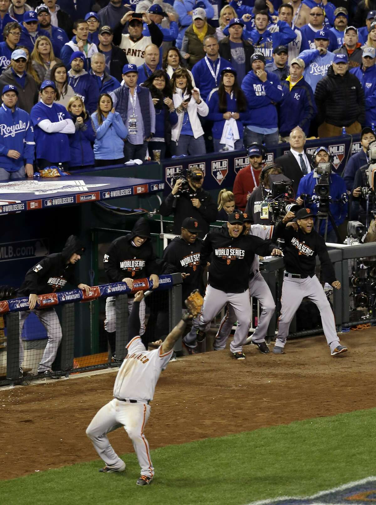 MIGHTY K.C. HAS POPPED OUT: A joyful Panda (Pablo Sandoval) falls backward after catching the final out in the ninth inning of Game 7 of the World Series.