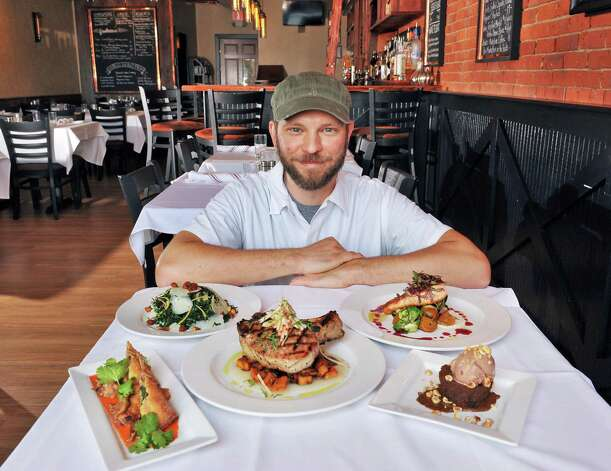 Chef Jeff Strom with a table full of his creations at Next Door Kitchen & Bar on Front Street Tuesday Oct. 28, 2014,in Ballston Spa, NY.  (John Carl D'Annibale / Times Union) Photo: John Carl D'Annibale / 00029223A