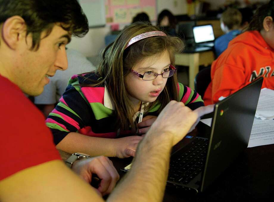 Para-professional Nick Coletti helps sixth-grader Nancy Stambaugh use a Chromebook laptop to research El Reno tornado at Western Middle School in Greenwich, Conn., on Thursday, October 30, 2014. Photo: Lindsay Perry / Stamford Advocate