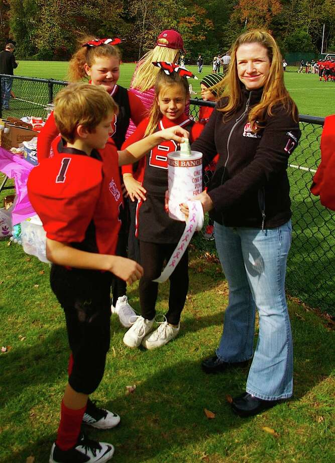 Throughout the month of October the Greenwich Youth Football League's BANC Raider family came together to raise awareness and money for Breast Cancer research. Players wore wear pink ribbon stickers on their helmets and cheerleaders led cheers with pink and white pom-pons. Cheerleaders also donated their time and talents, hosting a sideline bake sale each week. Every penny raised will be donated directly to Greenwich Breast Cancer Alliance to support research, early detection and local education. Pictured above, BANC Raider Will Macgillivray donates to get a pink ribbon sticker for his helmet, from Jenn Aravides ( BANC mom), as cheerleaders Kaycee Piro, Jillian Judge look on. Photo: Contributed Photo / Greenwich Time Contributed