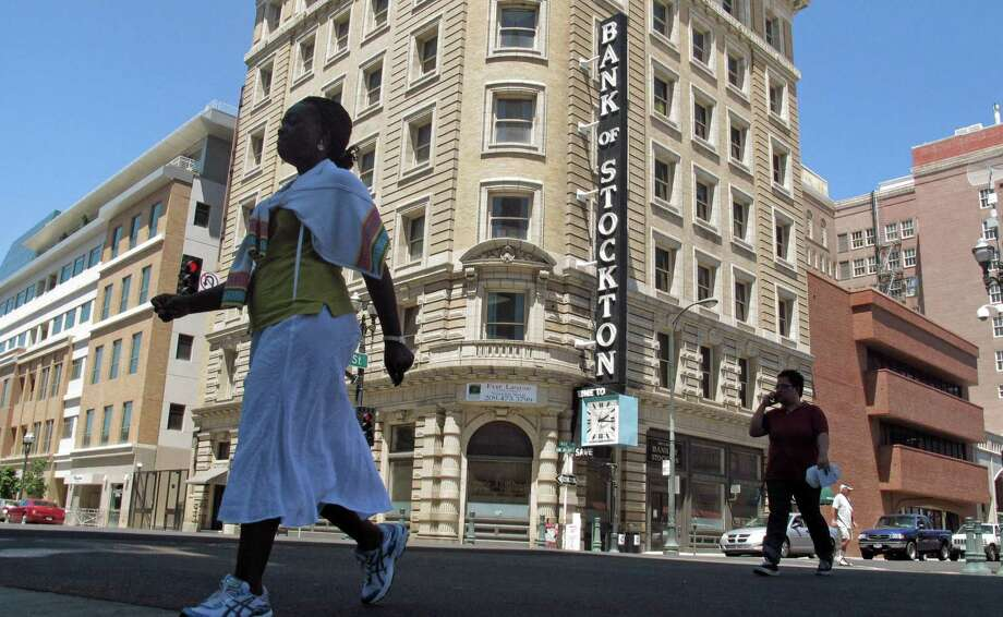 FILE  - In this June 27, 2012, file photo, pedestrians cross a street near the Bank of Stockton in Stockton, Calif. Photo: Gosia Wozniacka, STF / AP