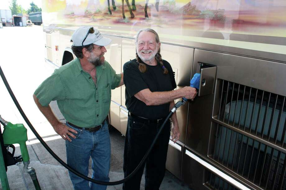 Willie Nelson pumps biodiesel into his bus on tour in Oregon in 2011. To his right is Bob King, the founder of Pacific Biodiesel.
