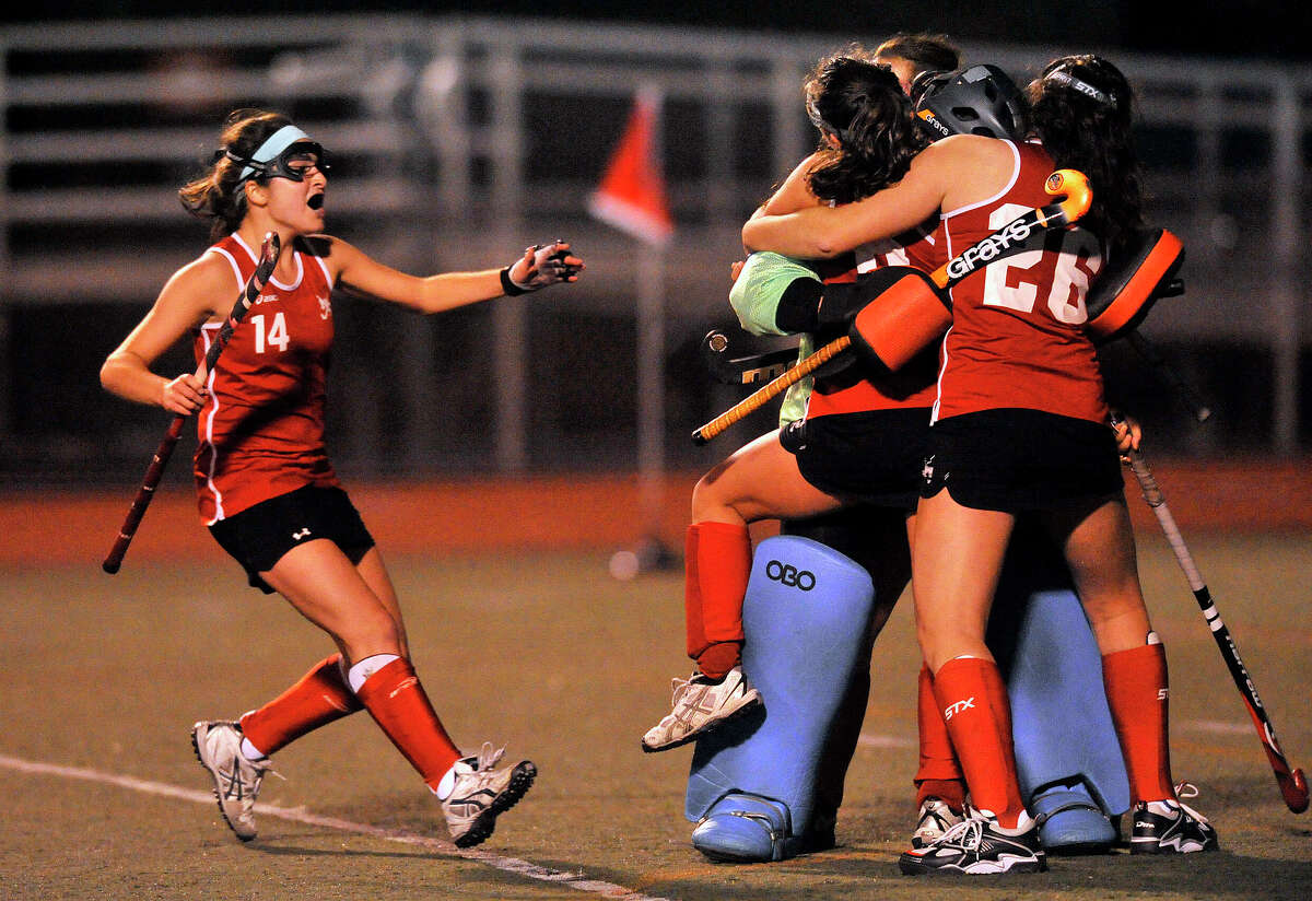 New Canaan's Isabel Taben, left, celebrates with her team mates after the clock runs out following their FCIAC field hockey championship game against Darien at Brien McMahon High School in Norwalk, Conn., on Thursday, Oct. 30, 2014. New Canaan took home the title beating Darien, 2-0.