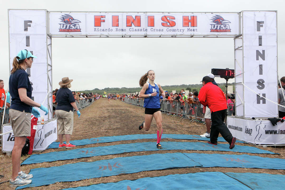 Paige Hofstad of New Braunfels crosses the finish line of the Gold Girls 5K during the UTSA Ricardo Romo Classic cross country meet at the National Shooting Complex on Sept. 20, 2014 .